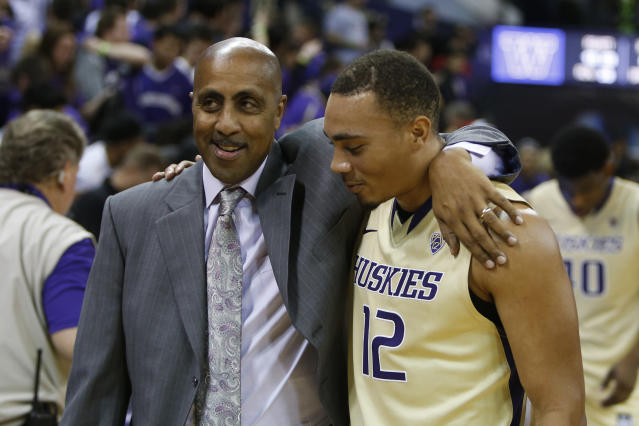 Washington head coach Lorenzo Romar, left, hugs guard Andrew Andrews (12) after an NCAA college basketball game, Sunday, Dec. 7, 2014, in Seattle, Wash. Washington beat San Diego State 49-36. (AP Photo/Jennifer Buchanan)