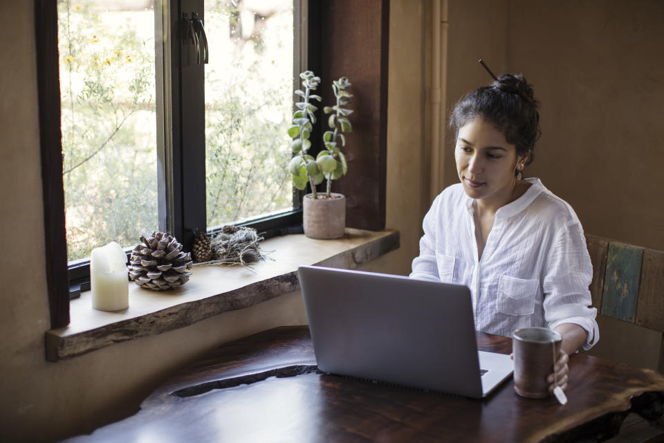 Young adult woman, multi-ethnic, wearing a white blouse with rolled-up sleeves, leans in while working on her laptop computer. The computer sits atop her redwood slab table. A mug of tea is next to her. She works next to a window, where sunlight and yellow wildflowers beckon from outdoors. On the window sill are pinecones and seed pods from her last hike, and a candle, and a green houseplant in a terra cotta pot. She appears calm yet determined to finish her project on deadline. She has dark brown hair styled in a casual bun with dark brown eyes and a half-smile showing dimples and a glimmer of earring dangling down. Working at home allows healthy work-life balance.