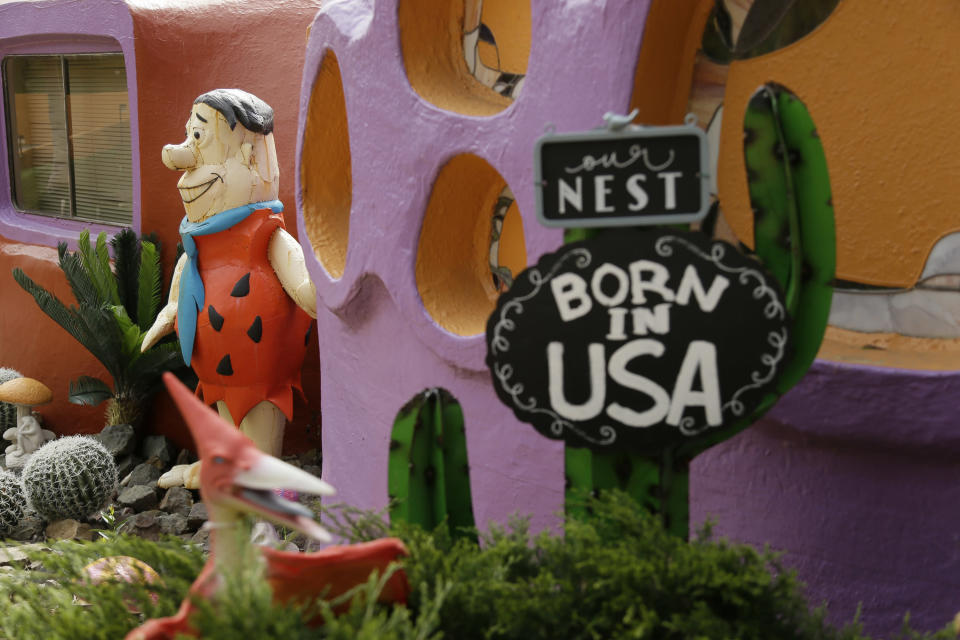 FILE - In this Thursday, April 11, 2019, file photo, a statue of Fred Flintstone stands near the front entryway of the Flintstone House in Hillsborough, Calif. Technically, the owner of the fanciful Flintstones house in a posh San Francisco suburb settled a lawsuit with the town of Hillsborough. But the agreement will allow Fred and his friends to remain. (AP Photo/Eric Risberg, File)