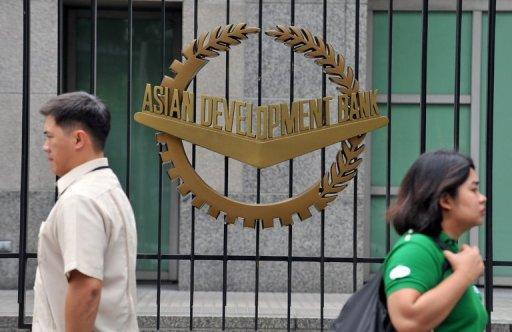 Pedestrians walk past a logo of the Asian Development Bank displayed outside its headquarters in Manila