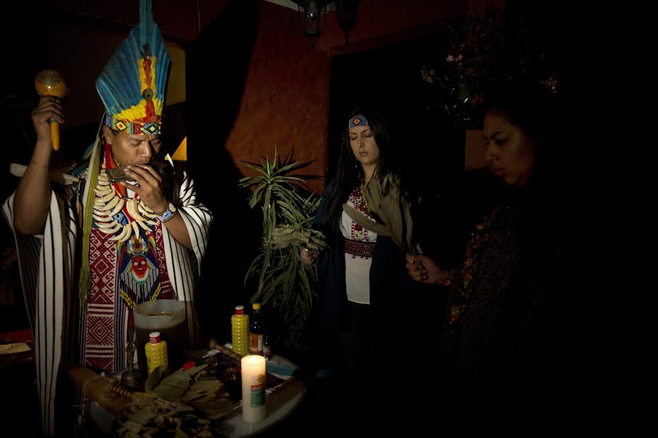 Picture taken on August 9, 2014 of a healer (L) starting a Yage ceremony  in La Calera, Cundinamarca department, Colombia. Yage, a mixture of the Ayahuasca hallucinogenic liana and a psychoactive bush, attracts many people in Colombia, who seek to participate in a traditional indigenous ritual of spiritual and physical healing impossible to realize in many countries where these plants are considered drugs. AFP PHOTO/EITAN ABRAMOVICH        (Photo credit should read EITAN ABRAMOVICH/AFP via Getty Images)