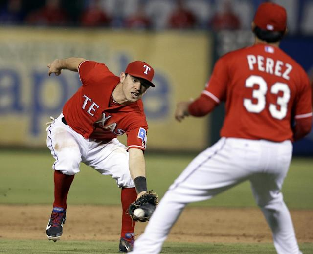 Texas Rangers second baseman Ian Kinsler, makes a catch behind the pitchers mound on a pop up by Seattle Mariners' Michael Morse as starting pitcher Martin Perez (33) watches in the sixth inning of a baseball game, Saturday, Aug. 17, 2013, in Arlington, Texas. (AP Photo/Tony Gutierrez)