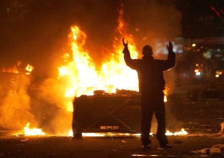FILE PHOTO: A protester reacts near burning police cars in central Yerevan March 2, 2008.  REUTERS/David Mdzinarishvili/Files