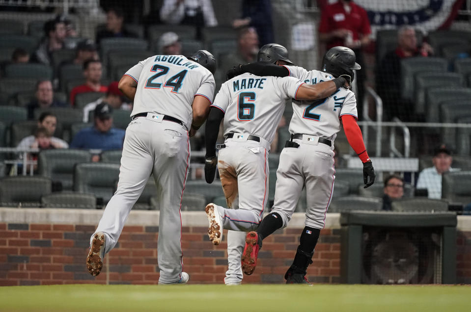 Miami Marlins' Jazz Chisholm Jr. (2) celebrates with Starling Marte (6) and Jesus Aguilar (24) after Chisholm hit a home run during the third inning of the team's baseball game against the Atlanta Braves on Wednesday, April 14, 2021, in Atlanta. (AP Photo/Brynn Anderson)