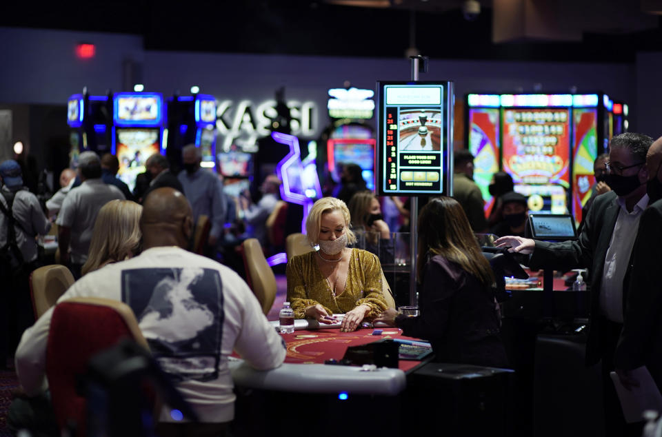 In this March 25, 2021, file photo, people gamble while wearing masks as a precaution against the coronavirus at the opening night of the Virgin Hotels Las Vegas in Las Vegas. On Saturday, May 1, casino capacity limits in Las Vegas increase to 80% and person-to-person distancing drops from 6 feet (1.8 meters) to 3 feet (0.9 meters). (AP Photo/John Locher, File)