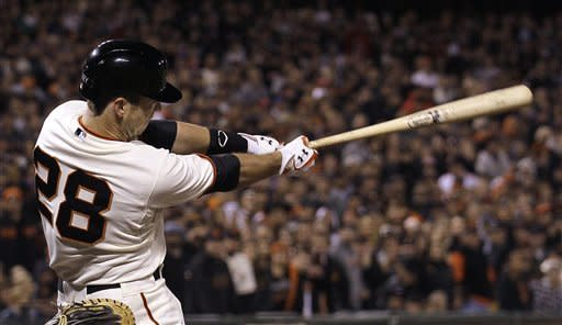 San Francisco Giants' Buster Posey singles off of Colorado Rockies pitcher Matt Belisle to score Gregor Blanco during the eighth inning of a baseball game in San Francisco, Monday, May 14, 2012. (AP Photo/Jeff Chiu)