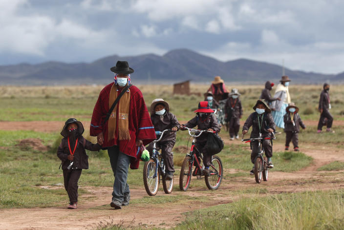 Aymaran Indigenous parents walk their children wearing new, protective uniforms to Jancohaqui Tana school as they return for their first week of in-person classes amid the COVID-19 pandemic, near Jesus de Machaca, Bolivia, Thursday, Feb. 4, 2021. (AP Photo/Juan Karita)