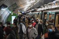 Commuters wearing face masks walk on the platform, of a Paris subway, Sunday Oct.25, 2020. A curfew intended to curb the spiraling spread of the coronavirus, has been imposed in many regions of France including Paris and its suburbs. (AP Photo/Lewis Joly)