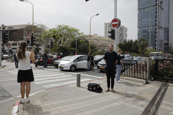Israelis stand still next to their cars as a siren sounds in memory of victims of the Holocaust, in Tel Aviv, Israel, Thursday, May 2, 2019. Israel has come to a standstill as people stopped in their tracks for a two-minute siren that wailed across the country in remembrance of the Holocaust's 6 million Jewish victims. (AP Photo/Sebastian Scheiner)