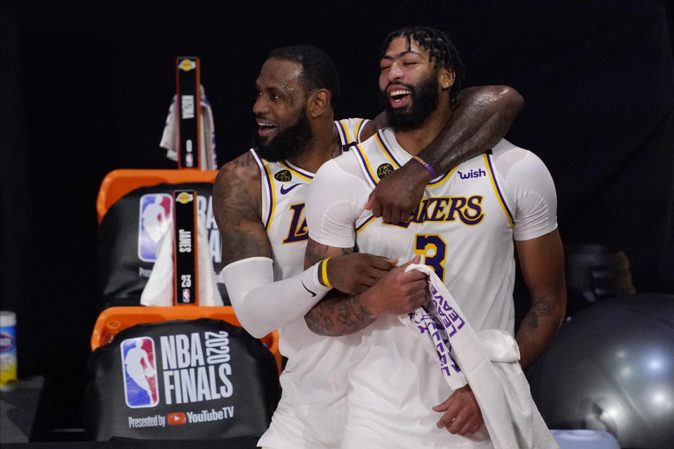 Los Angeles Lakers' LeBron James (23) and Anthony Davis (3) celebrate after the Lakers defeated the Miami Heat 103-88 in Game 6 of basketball's NBA Finals Sunday, Oct. 11, 2020, in Lake Buena Vista, Fla. (AP Photo/Mark J. Terrill)