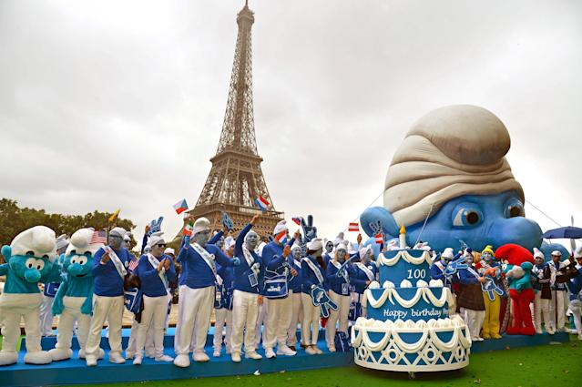 BRUSSELS, BELGIUM - JUNE 22: Smurf Ambassadors pose by a giant Smurf character as part of Global Smurfs Day celebrations on June 22, 2013 on the Seine river bank in Paris, France. The Eiffel tower is seen behind. (Photo by Pascal Le Segretain/Getty Images for Sony Pictures Entertainment)