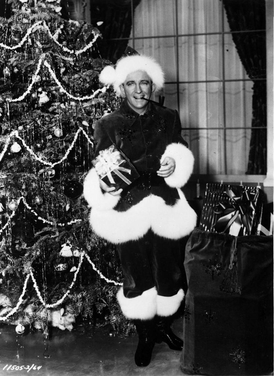 <p>The acclaimed Christmas-song performer poses next to a yuletide tree, donning a Santa costume, in 1954.</p>