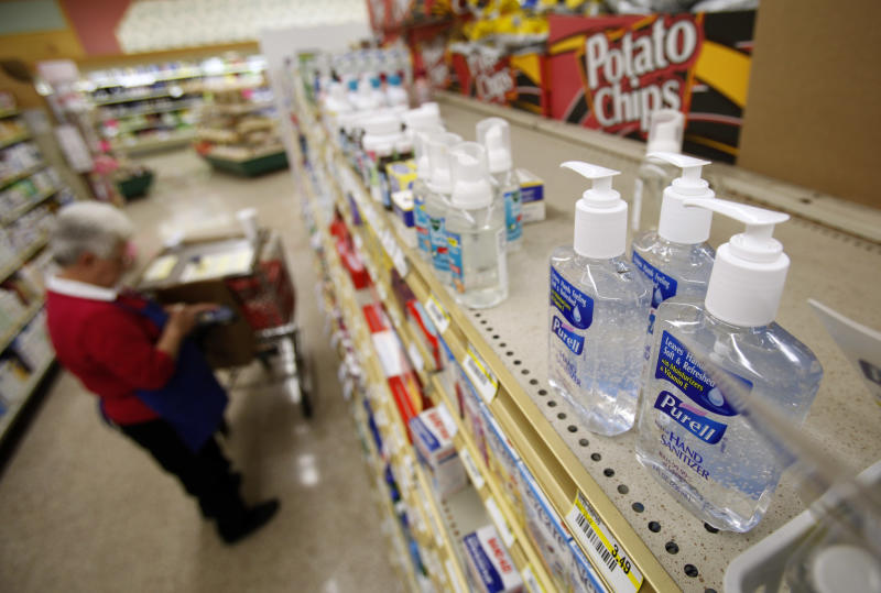 Bottles of Purell hand sanitizer sit on display as a worker stocks shelves at a local Dahl's grocery store, Wednesday, April 29, 2009, in Des Moines, Iowa. (AP Photo/Charlie Neibergall)