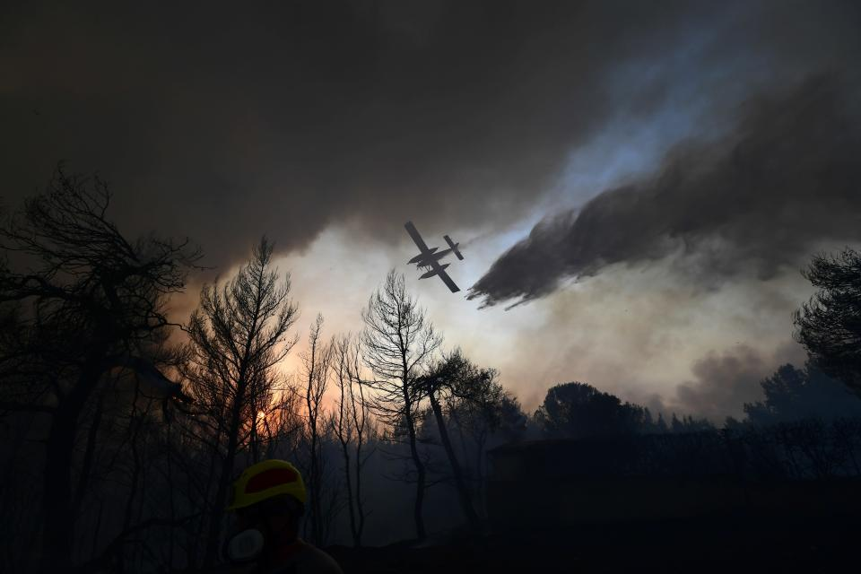 An aircraft drops water during a wildfire in Kryoneri area, northern Athens, Greece, Thursday, Aug. 5, 2021. Wildfires rekindled outside Athens and forced more evacuations around southern Greece Thursday as weather conditions worsened and firefighters in a round-the-clock battle stopped the flames just outside the birthplace of the ancient Olympics. (AP Photo/Michael Varaklas)