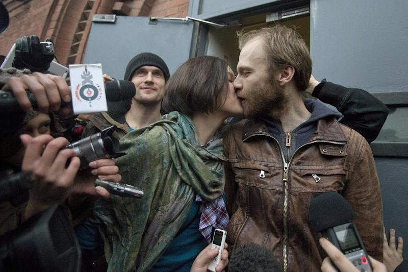 "Russian freelance photographer Denis Sinyakov, center, kisses his wife Alina Zhiganova, outside the gates of ""Kresty"" St. Petersburg prison, after he was released in St. Petersburg, Russia, Thursday, Nov. 21, 2013. Two more of the 30 people arrested by Russia following a Greenpeace protest in the Arctic two months ago have been freed on bail. Sinyakov and activist Andrei Allakhverdov walked out of a detention center on Thursday. The 30 were arrested in September after a Greenpeace ship, the Arctic Sunrise, entered Arctic waters despite Russian warnings. (AP Photo/Pavel Golovkin)"