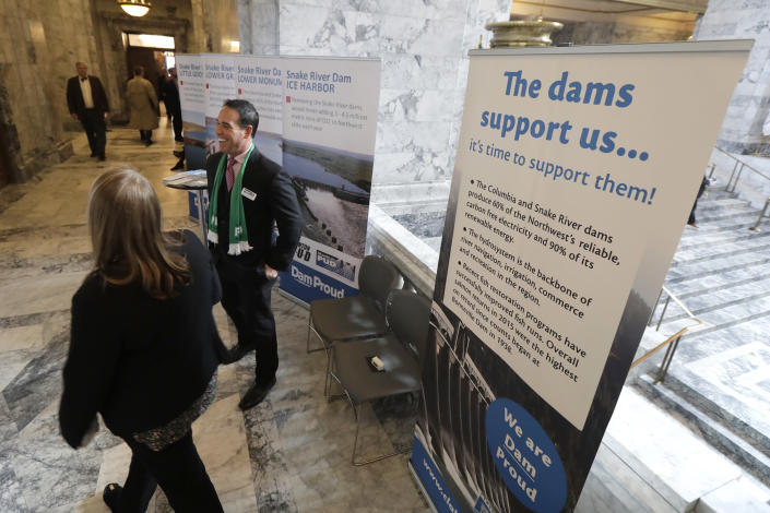 In this Feb. 12, 2020, photo, Mike Gonzalez, center, senior manager of public affairs at the Franklin Public Utility District, stands next to informational signs promoting dams on the Snake River during a lobby day at the Capitol in Olympia, Wash. A federal report released Friday, Feb. 28, rejected the idea of removing four hydroelectric dams on a major Pacific Northwest river in a last-ditch effort to save threatened and endangered salmon. The report says breaching the dams would destabilize the power grid, increase greenhouse emissions and raise the risk of power outages. (AP Photo/Ted S. Warren)
