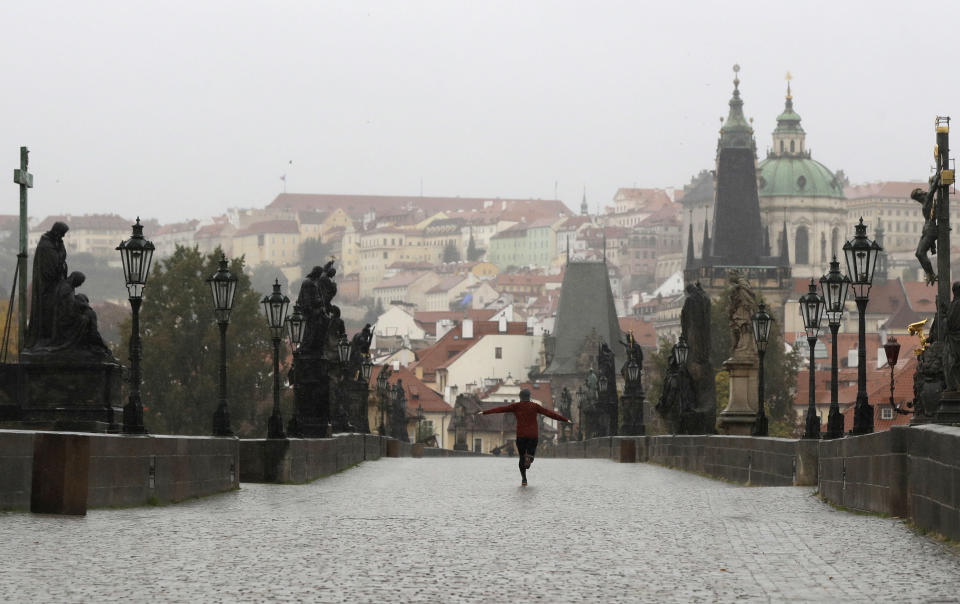 A man runs across an empty medieval Charles Bridge in Prague, Czech Republic, Wednesday, Oct. 14, 2020. The Czech Republic has imposed a new series of restrictive measures in response to a record surge in coronavirus infections. Starting Wednesdays all bars and restaurants can only sell takeaway while drinking of alcohol is banned at public places. (AP Photo/Petr David Josek)