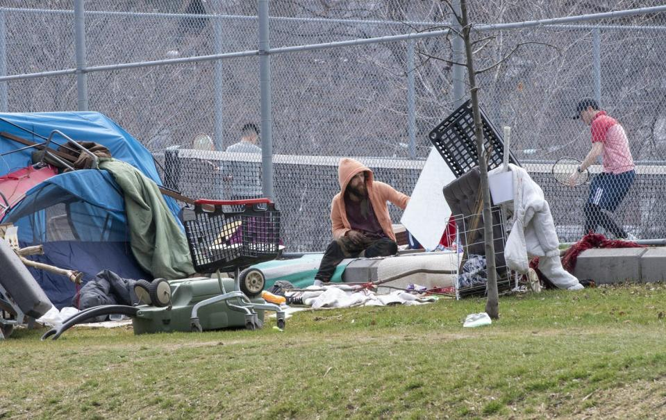 A man sitting in front of a tennis court, next to a tent and shopping carts.