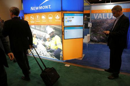 FILE PHOTO: Visitors pass the Newmont Mining Corporation booth during the Prospectors and Developers Association of Canada (PDAC) annual convention in Toronto, Ontario, Canada March 4, 2019. REUTERS/Chris Helgren/File Photo