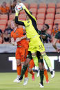 Portland Timbers goalkeeper Aljaz Ivacic (31) makes the save over Houston Dynamo defender Tim Parker (5) and defender Zac McGraw, right, during the second half of an MLS soccer match Wednesday, June 23, 2021, in Houston. (AP Photo/Michael Wyke)