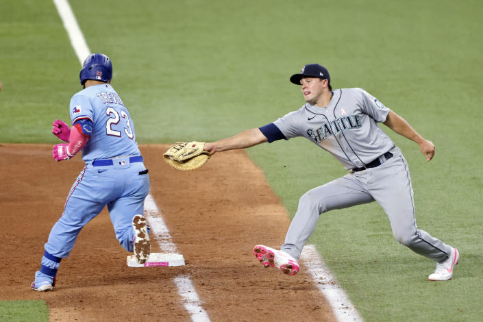 Texas Rangers catcher Jose Trevino (23) evades a tag by Seattle Mariners first baseman Evan White (12) as he makes it safely to first during the fifth inning of a baseball game Sunday, May 9, 2021, in Arlington, Texas. (AP Photo/Michael Ainsworth)