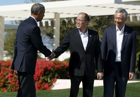 U.S. President Barack Obama (L) shake hands with Philippine President Benigno Aquino as Singapore Prime Minister Lee Hsien Loong looks on as the leaders from the 10-nation Association of Southeast Asian Nations (ASEAN) summit finish taking a family photo in Rancho Mirage, California, February 16, 2016.    REUTERS/Mike Blake