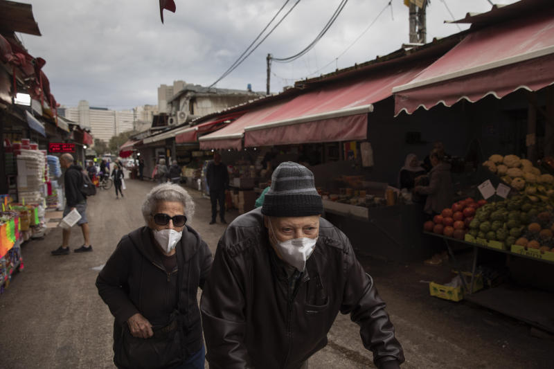 An elderly couple wear face masks as they shop at a food market in Tel Aviv, Israel, Tuesday, March 17, 2020. The head of Israel's shadowy Shin Bet internal security service said Tuesday that his agency received Cabinet approval overnight to start deploying its counter-terrorism tech measures to help curb the spread of the new coronavirus in Israel. For most people, the virus causes only mild or moderate symptoms. For some it can cause more severe illness. (AP Photo/Oded Balilty)