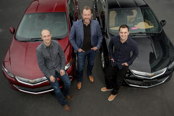 The three are standing with two Chevrolet Volt sedans.