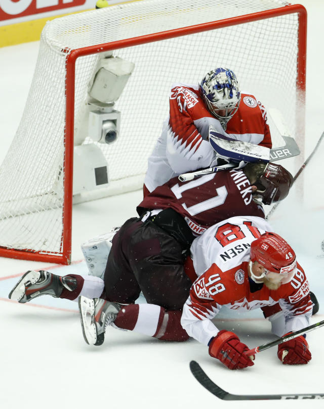 Latvia's Kristaps Sotnieks, center, collides with Denmark's Nicholas Jensen, front and Denmark's Frederik Andersen, back, during the Ice Hockey World Championships group B match between Denmark and Latvia at the Jyske Bank Boxen arena in Herning, Denmark, Tuesday, May 15, 2018. (AP Photo/Petr David Josek)