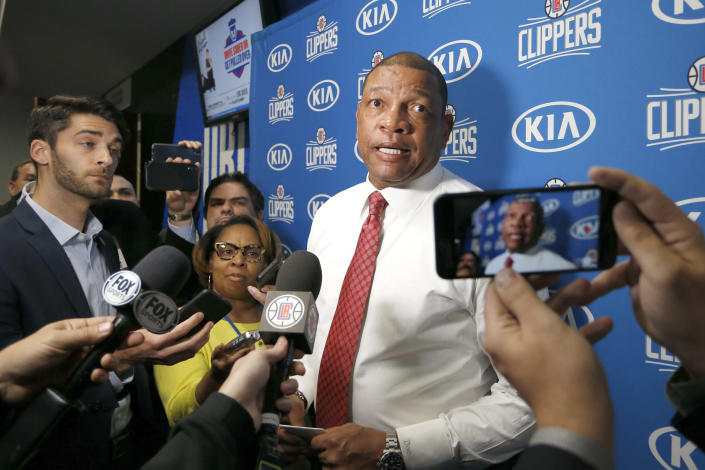 """FILE- In this Jan. 26, 2020 file photo, Los Angeles Clippers head coach Doc Rivers talks with the media after an NBA basketball game against the Orlando Magic in Orlando, Fla. Rivers informed the media that there will be no interviews in the locker room that night as his players dealt with the loss of Kobe Bryant. River's remark to reporters, """"We are all Lakers today,"""" holds the number 10 position on the Yale Law School librarian's list of the most notable quotes of 2020. (AP Photo/Reinhold Matay, File))"""