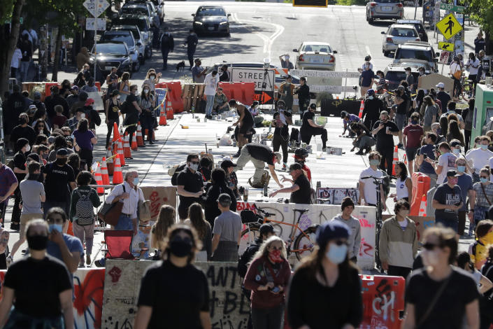 """FILE - In this June 11, 2020, file photo artists paint large letters that read """"Black Lives Matter"""" painted on a street near Cal Anderson Park inside what is being called the """"Capitol Hill Autonomous Zone"""" in Seattle. (AP Photo/Ted S. Warren, File)"""