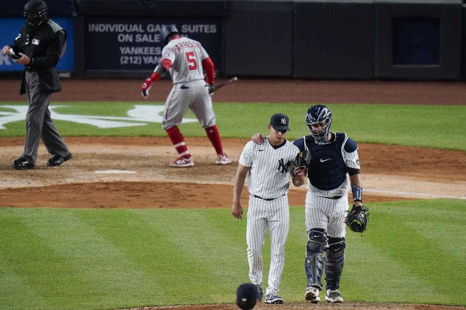 New York Yankees catcher Gary Sanchez, right, talks to Jonathan Loaisiga during the eighth inning of a baseball game as Washington Nationals' Josh Harrison (5) waits near the plate, Friday, May 7, 2021, in New York. (AP Photo/Frank Franklin II)
