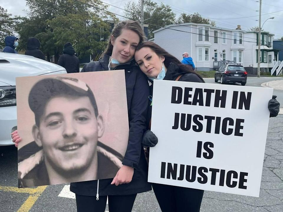 Samantha (left) and Courtney Pike stand outside the of the HMP to protest lack of addiction help after their brother died by suicide.  (Meg Roberts/CBC - image credit)