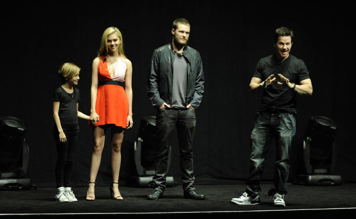 """Mark Wahlberg, right, a cast member in the upcoming film """"Transformers: Age of Extinction,"""" addresses the audience as fellow cast members Nicola Peltz, second from left, and Jack Reynor, third from left, and Wahlberg's daughter Ella look on during the Opening Night Presentation from Paramount Pictures at CinemaCon 2014 on Monday, March 24, 2014, in Las Vegas. (Photo by Chris Pizzello/Invision/AP)"""