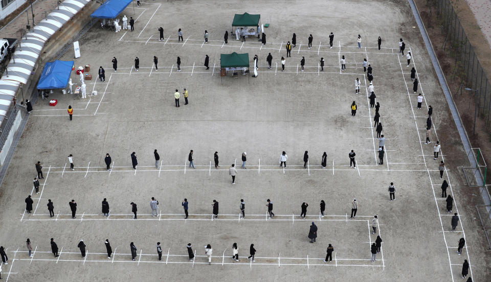 High school students and staff wait in line to receive the coronavirus tests at a makeshift clinic set up on a playground of a school in Sejong, South Korea, Friday, Nov. 27, 2020. South Korea's daily virus tally hovered above 500 for the second straight day, as the country's prime minister urged the public to stay home this weekend to contain a viral resurgence. (Kim Ju-hyung/Yonhap via AP)
