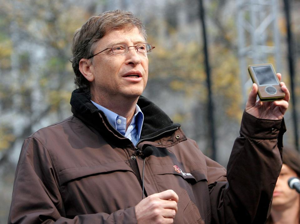 Microsoft chairman Bill Gates shows off the Zune media player to a crowd at a launch party in downtown Seattle November 13, 2006. The 30-gigabyte player, which goes on sale to the public November 14th, features wireless technology, a built-in FM radio and three-inch screen that can play both music and videos. REUTERS/Robert Sorbo (UNITED STATES)
