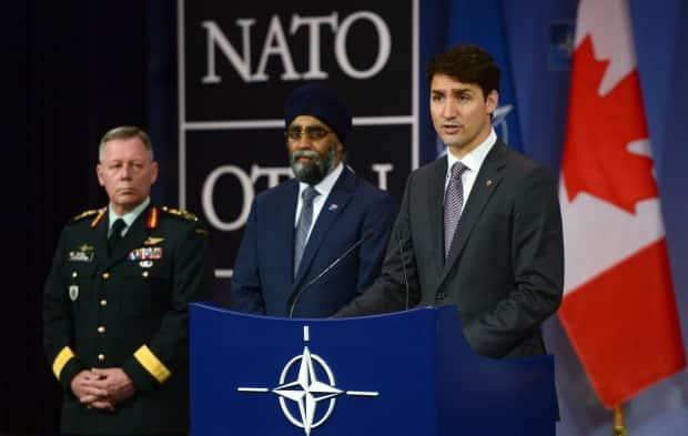 Prime Minister Justin Trudeau, right, stands with Defence Minister Minister Harjit Singh Sajjan, centre, and then-Chief of the Defence Staff Gen. Jonathan Vance during a press conference at NATO headquarters in Brussels, Belgium on May 25, 2017. (Sean Kilpatrick/Canadian Press - image credit)