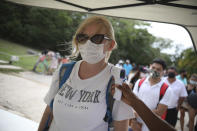 A tourist, wearing a protective face mask, stands still as an employee measures her body temperature as a preventive measure amid the new coronavirus pandemic, upon her arrival to the Mayan ruins in Tulum, Quintana Roo state, Mexico, Tuesday, Jan. 5, 2021.(AP Photo/Emilio Espejel)