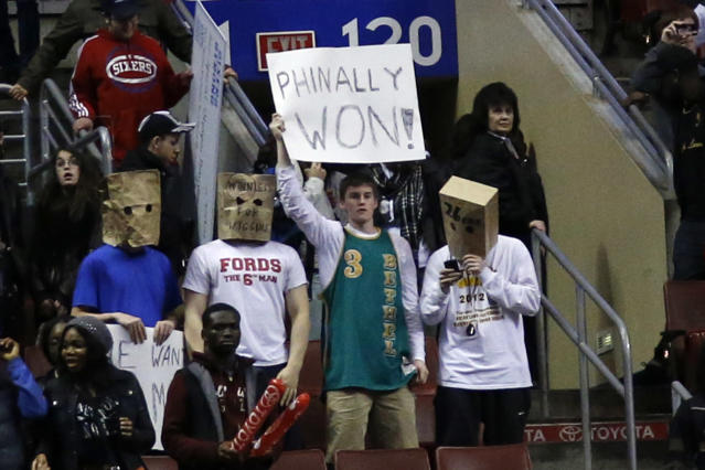 Fans hold signs after the Philadelphia 76ers won an NBA basketball game against the Detroit Pistons, Saturday, March 29, 2014, in Philadelphia. Philadelphia won 123-98, breaking a 26-game losing streak. (AP Photo/Matt Slocum)