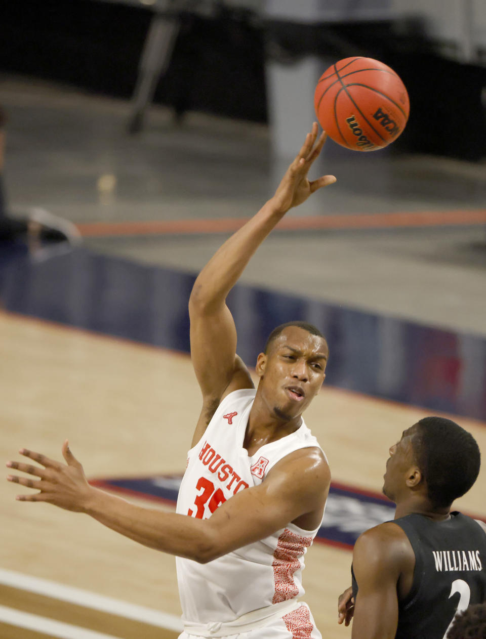Houston forward Fabian White Jr. (35) makes a pass over Cincinnati guard Keith Williams (2) during the first half of an NCAA college basketball game in the final round of the American Athletic Conference men's tournament Sunday, March 14, 2021, in Fort Worth, Texas. (AP Photo/Ron Jenkins)