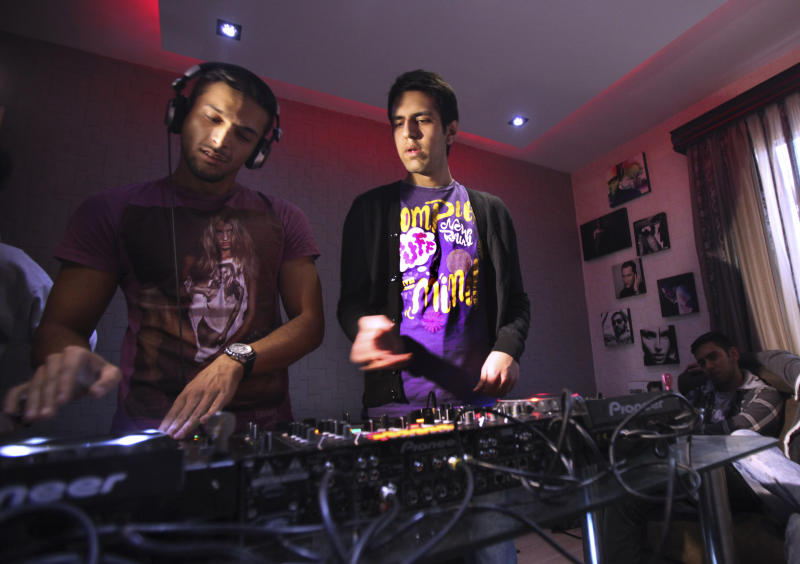"""In this picture taken on Wednesday, Feb. 13, 2013, Iranian musicians Pedram, left, and Soheil, members of a band called """"Rebeat,"""" compose remixes of folk songs on their electronic mixing console in Tehran, Iran. Headphone-wearing disc jockeys mixing beats. It's an underground music scene that is flourishing in Iran, despite government restrictions. (AP Photo/Vahid Salemi)"""