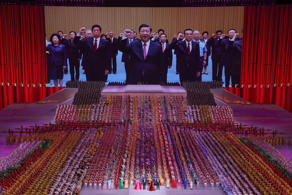 Xi Jinping again pictured centre on screen in front of a crowd of people.