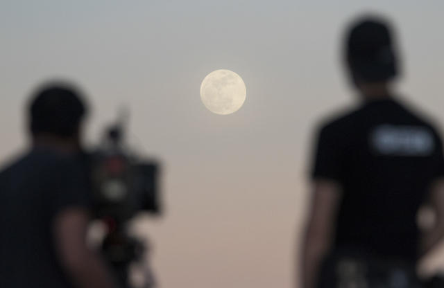 <p>Ultimate Fighter Championship videographers Silton Buen Dia, left, and Chris Warner film the moon in Las Vegas on Tuesday, Jan 30, 2018. (Photo: Richard Brian/Las Vegas Review-Journal via AP) </p>
