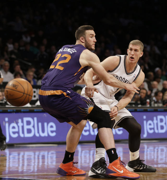 Brooklyn Nets's Mason Plumlee, right, passes around Phoenix Suns' Miles Plumlee during the first half of the NBA basketball game at the Barclays Center Monday, March 17, 2014 in New York. (AP Photo/Seth Wenig)