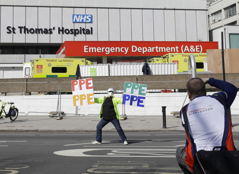 A woman holding up signs (PPE-Personal Protection Equipment) is photographed as she stands outside St Thomas' Hospital in central London as British Prime Minister Boris Johnson is in intensive care fighting the coronavirus in London, Tuesday, April 7, 2020. Johnson was admitted to St Thomas' hospital in central London on Sunday after his coronavirus symptoms persisted for 10 days. Having been in hospital for tests and observation, his doctors advised that he be admitted to intensive care on Monday evening. The new coronavirus causes mild or moderate symptoms for most people, but for some, especially older adults and people with existing health problems, it can cause more severe illness or death.(AP Photo/Kirsty Wigglesworth)