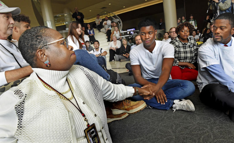 In this Oct. 25, 2018, photo Aura Wharton-Beck, left, an assistant professor in the School of Education at the University of St. Thomas and a graduate of the school, clasps hands with Kevyn Perkins, center, during a moment of silence before a protest in the Anderson Student Center at the University of St. Thomas in St. Paul, Minn. The protest was in response to a racial slur written on the dorm door of Perkins, a University of St. Thomas freshman, on Oct. 19. At right is St. Paul mayor Melvin Carter. (Jean Pieri/Pioneer Press via AP)