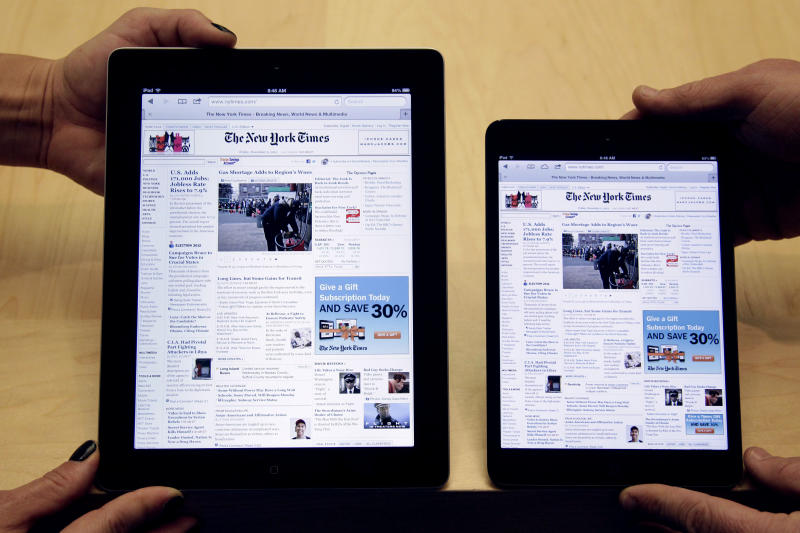 FILE -In this Friday, Nov. 6, 2012, file photo, employees hold a new full size Apple iPad 4th generation, left, next to new Apple iPad mini at the Apple store on Michigan Ave. in Chicago. The new iPad Mini is sure to please millions this holiday season. But fans of the latest full-size iPad have reason to look down on this newcomer: compared to other Apple products, the screen just isn't that good. (AP Photo/M. Spencer Green)