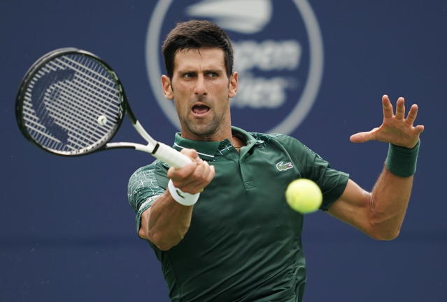 Novak Djokovic, of Serbia, returns a shot to Peter Polansky, of Canada, during the Rogers Cup men's tennis tournament in Toronto, Wednesday, Aug. 8, 2018. (Mark Blinch/The Canadian Press via AP)