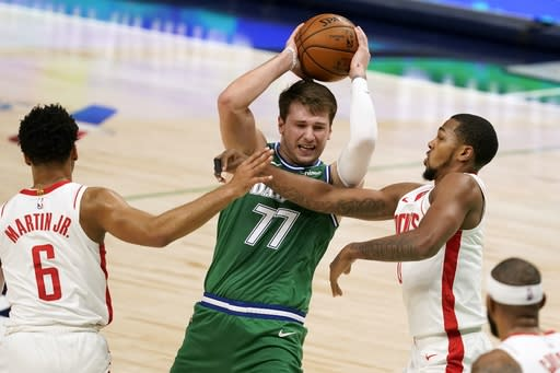 Houston Rockets forward Kenyon Martin Jr. (6) and guard Sterling Brown, right, defend against Dallas Mavericks' Luka Doncic (77) during the first half of an NBA basketball game in Dallas, Saturday, Jan. 23, 2021. (AP Photo/Tony Gutierrez)