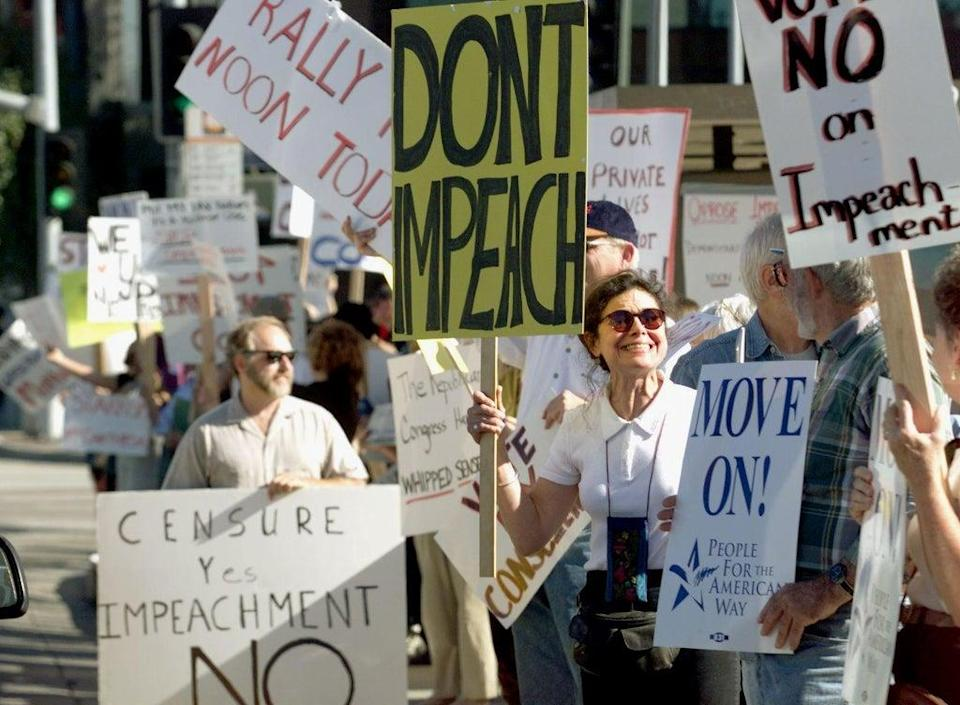 A  group of people demonstrate to stop the impeachment process against Bill Clinton on 16 December 1998 (HECTOR MATA/AFP via Getty Images)